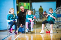 Three girls seated on chairs playing boccia with adult coach