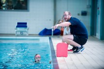 Young female swimmer in the pool being coached by Paul Wilson from Scottish Swimming on poolside