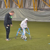 Participant using walking frame with coach teaching dribbling skills