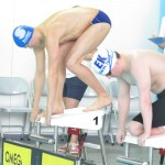 Two swimmers preparing to dive at the championships