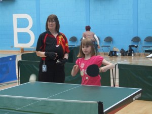 Young girl playing table tennis with coach