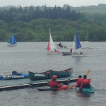 Participants in canoes and boats on the water