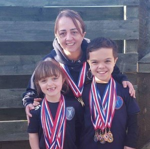 Hailey, Finlay and Skye with their collection of medals