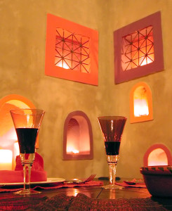 Moroccan-themed dining room with alcoves, windows and a wine glass.
