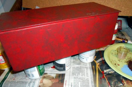 Brown paint sponged over the red base of the sides and bottom.