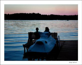 A couple sit on a bench on a pier looking over the water