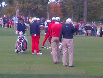 Tiger Woods stands amongst a group of golfers at a PGA Tournament