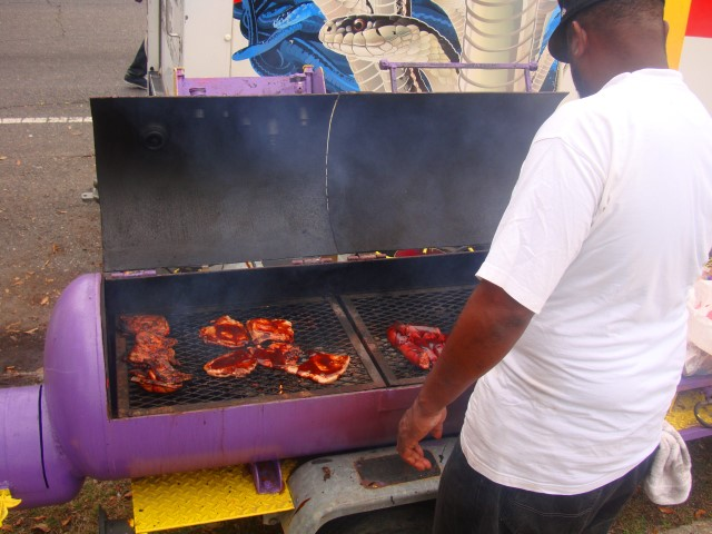 Streetside barbecue man vending pork chop sandwiches