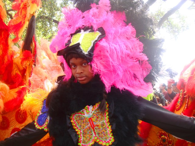 Beautiful Mardi Gras Indian girl shyly vamping