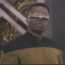 Ein Schwarzer Mann in einer schwarz-goldenen Uniform und mit einem futuristischem Gerät über den Augen.