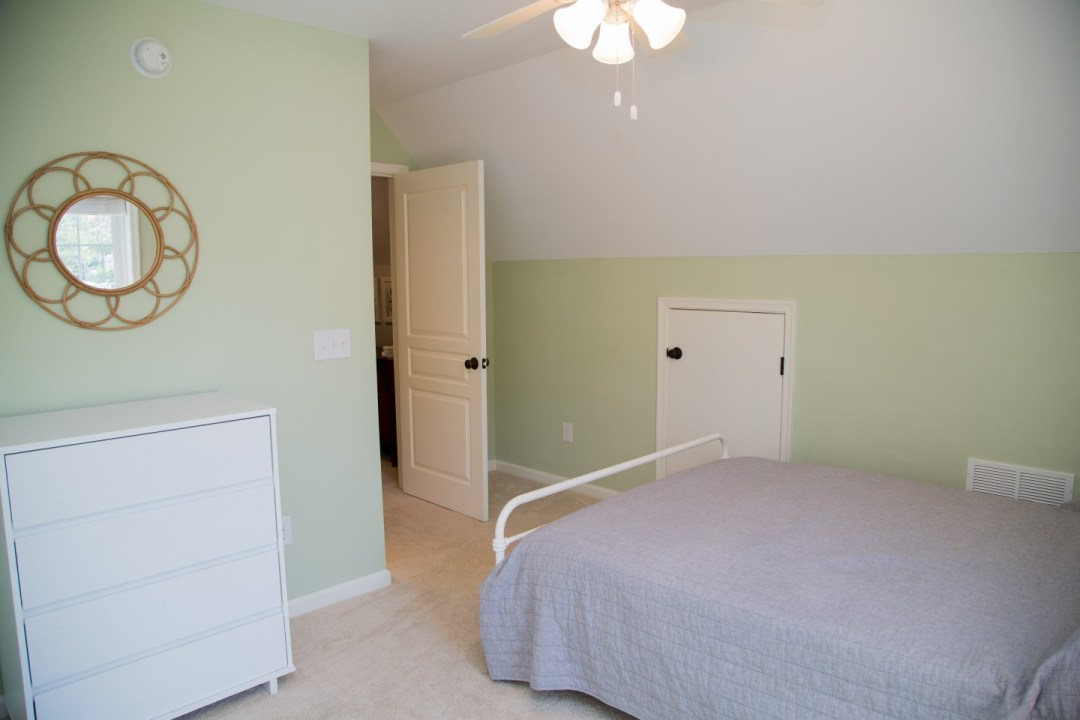 Bedroom with Light Green Wall Paint, Round Flower Style Mirror and White Flat Panel Cabinet