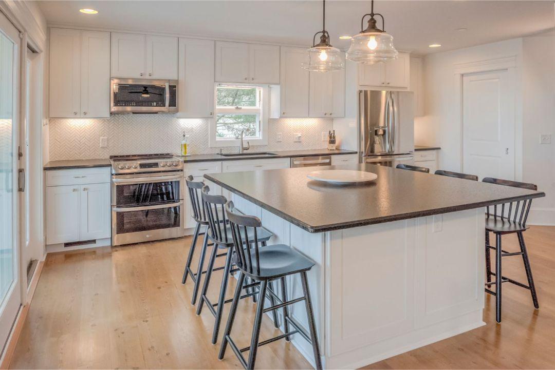 Kitchen Renovation in Dune Road, Bethany Beach DE - Kitchen with Center Island with White Vanities and Dark Granite Countertop