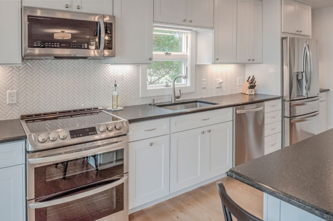 Kitchen with Stainless Steel Appliances and White Vanities and Backsplash