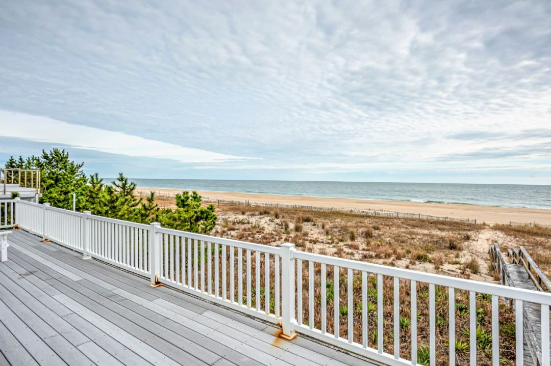 Deck with White Railing and Beach View