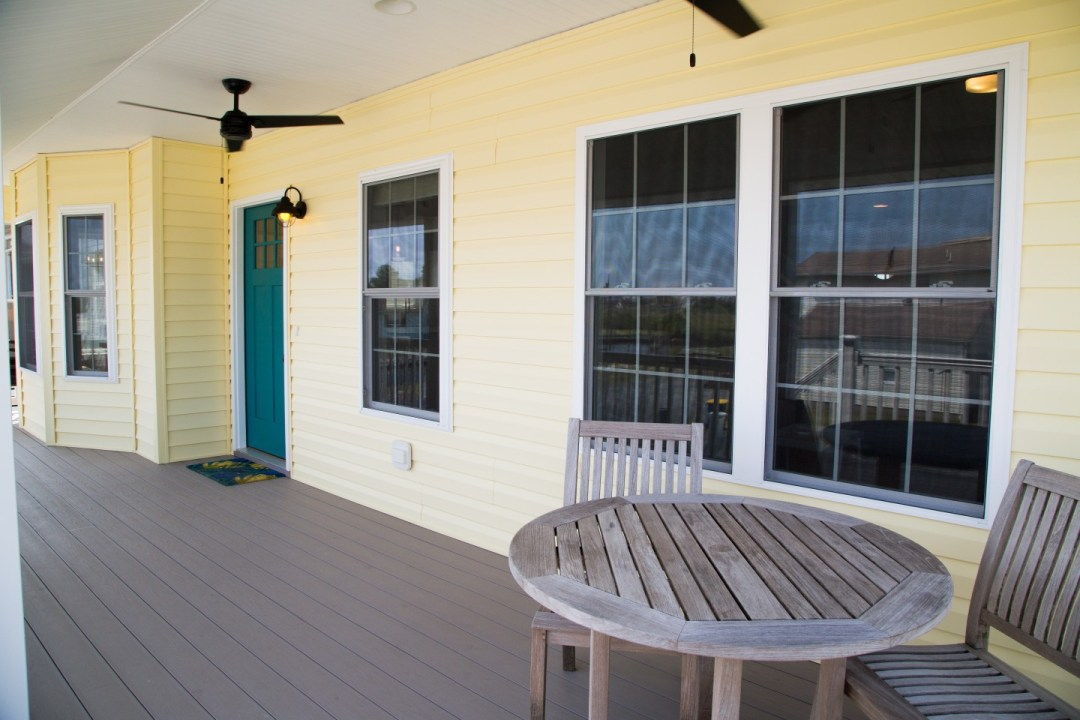 Exterior Porch with Yellow Siding, Wooden Round Table and Chairs