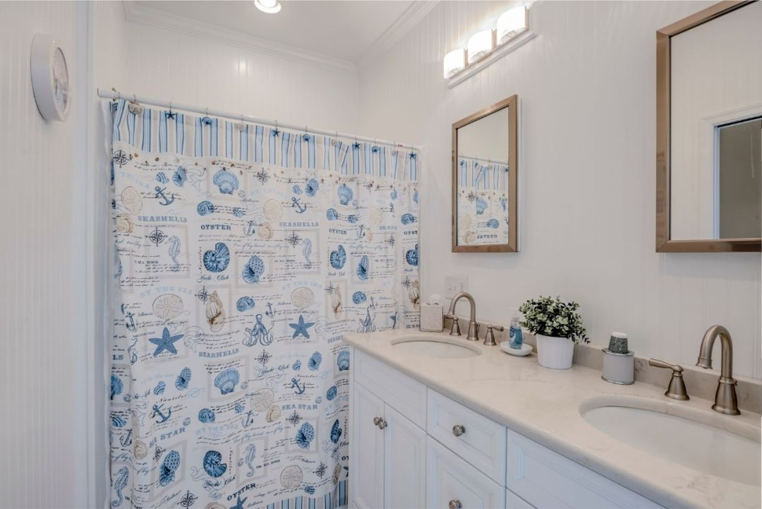Bathroom with Sea Themed Shower Curtain and White Vanities