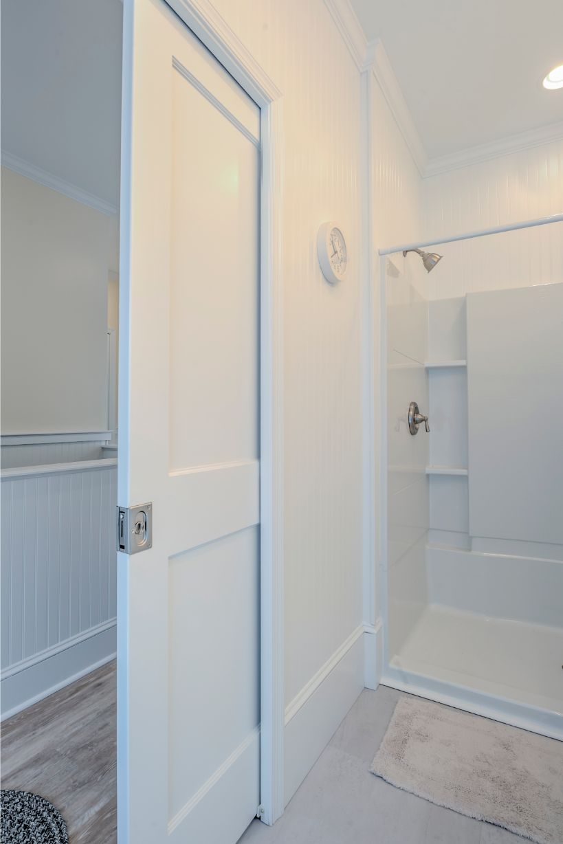 White Sliding Wooden Door Separating Bathroom from Hallway