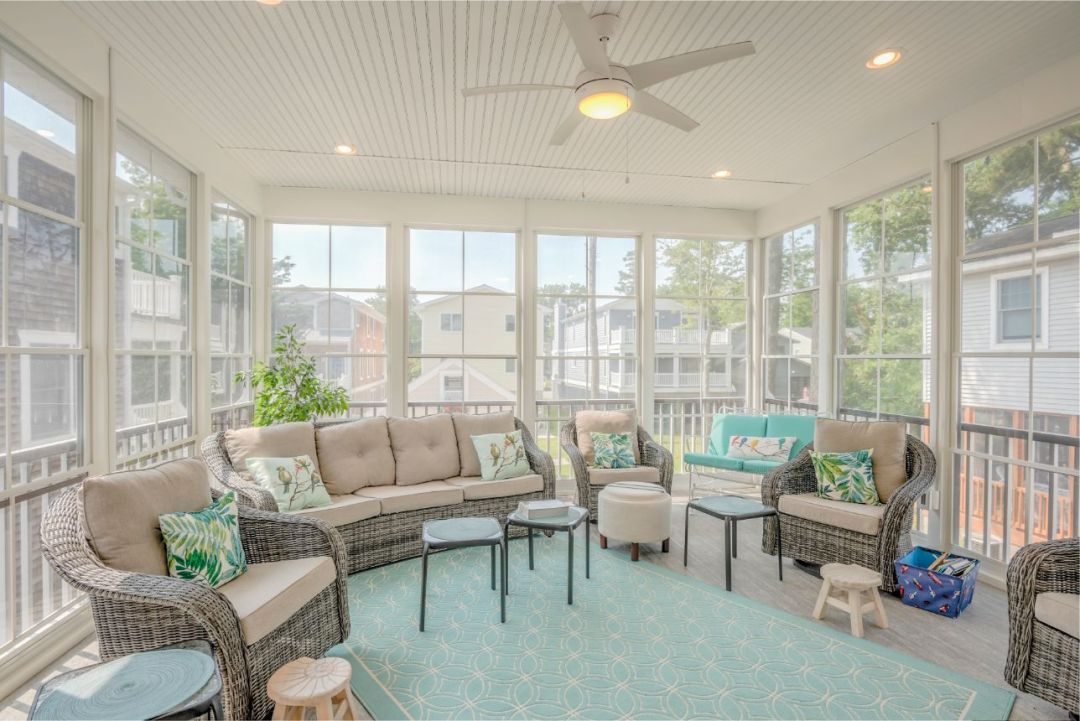 Sunroom with Rattan Furniture and Teal Accents