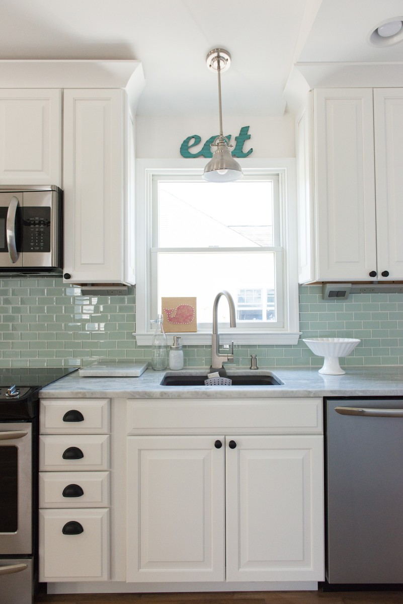 Kent Renovation Bethany Beach, DE Kitchen with Large Window, Matte Steel Pendant Light, Undermount Sink and White Cabinets