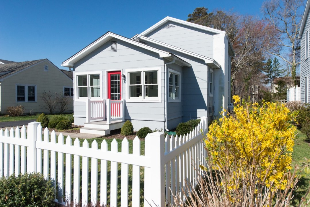 Kent Renovation Bethany Beach, DE Sunroom Exterior View with White Fence and Red Storm Door