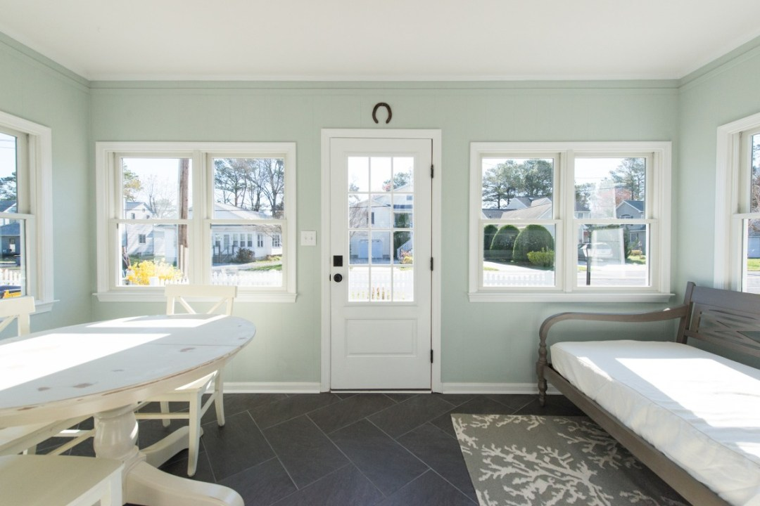 Kent Sunroom Renovation in Bethany Beach DE with Storm Door, Dark Floor Tiles, Wood Bench Seat and Light Sea Foam Wall Paint