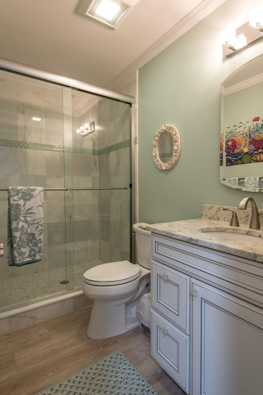 Bathroom Remodel in Kings Grant, Fenwick Island DE with Sliding Glass Shower Doors, Wood Flooring and White Vanity