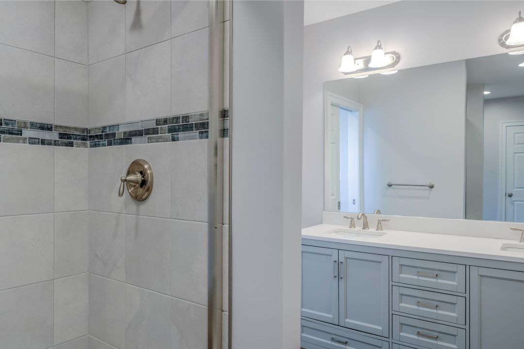 Bathroom Remodel in October Glory, Ocean View DE with White Shower Tiles, Blue Denim Mosaic Accent Tiles and White Vanities