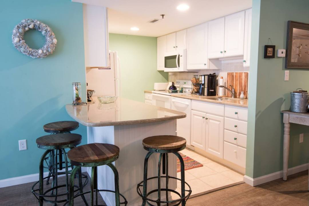 Sea Colony Condo Renovation Bethany Beach, DE with White Cabinets, Granite Countertop and Wood Floor