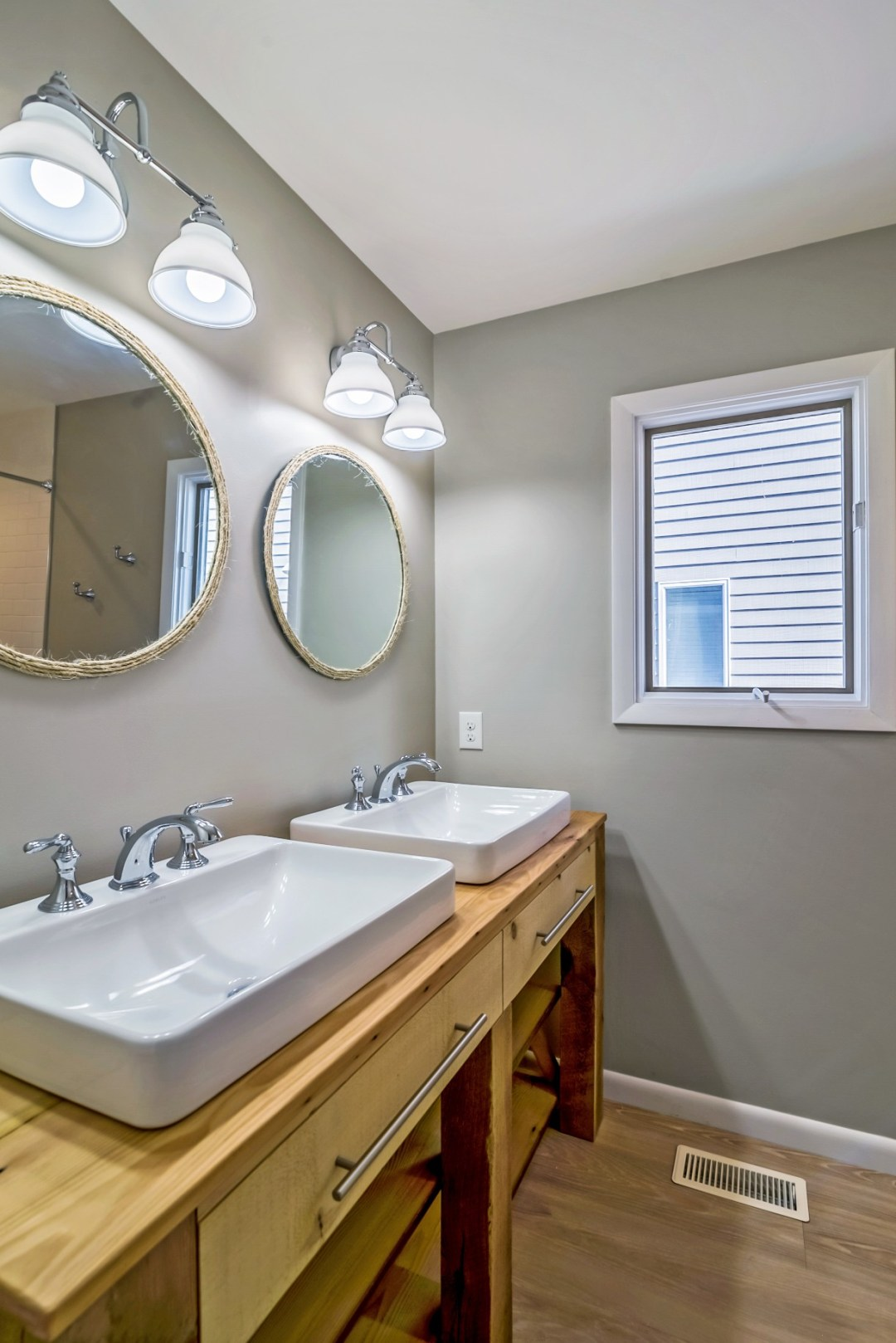 Bathroom Remodel in Wellington Parkway, Bethany Beach DE with Dual Sinks, Two Round Mirrors and Light Wood Vanities