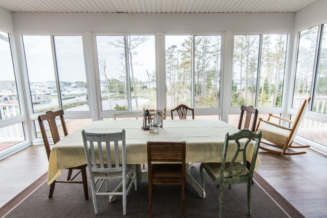 Whitesview Court House Lift New Addition in Ocean View DE Four Season Sunroom with Wood Flooring, Large Table and Rocking Chair