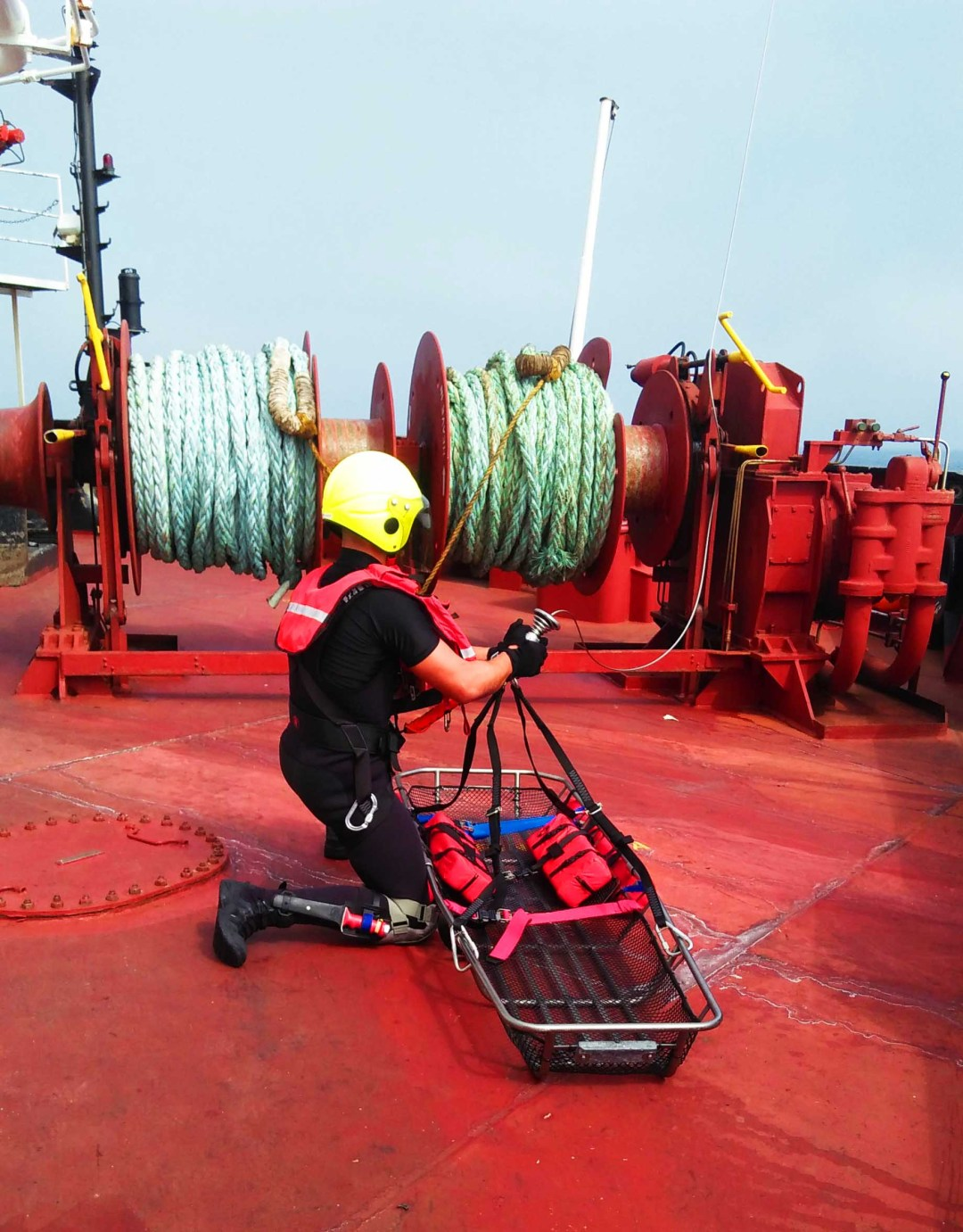 Search and Rescue Volunteer landing on the poop deck of a ship with stretcher