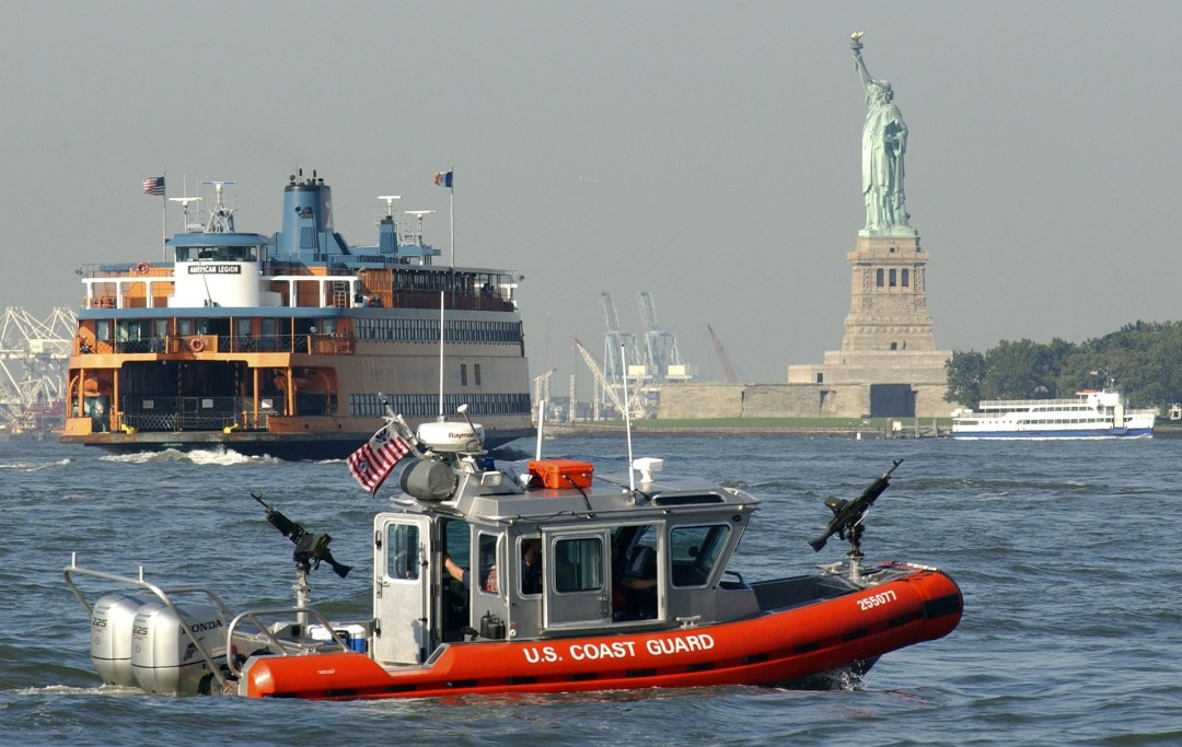 Statue of Liberty in New York Bay with ferries crossing and a US Coast Guard on Stand By.