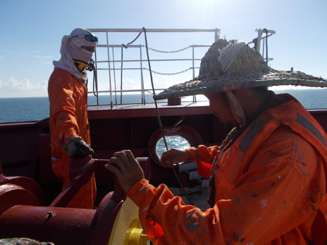 Deck crew preparing forward for working aloft on the ship's bulbous bow.
