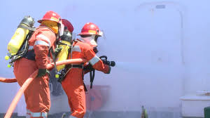 fire fighters with firehose and nozzles extinguishing flames on board ship. This task is included in maritime training centers.