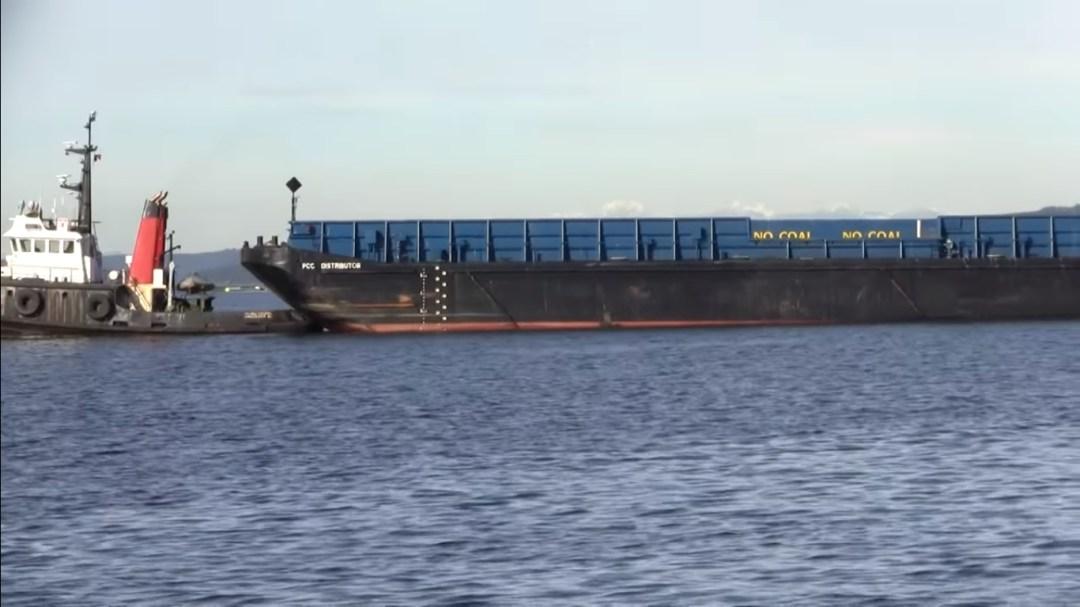 Harbor tug towing dumb barge