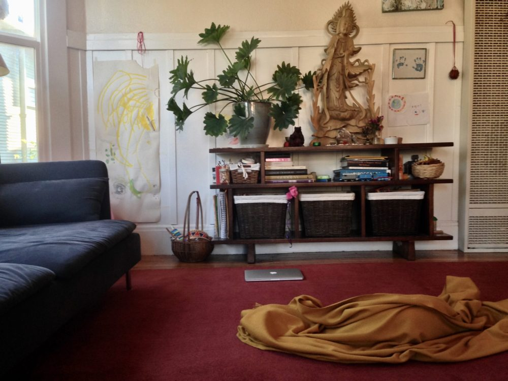 a cozy living room with red rug, Quan Yin statue, and meditation cushion