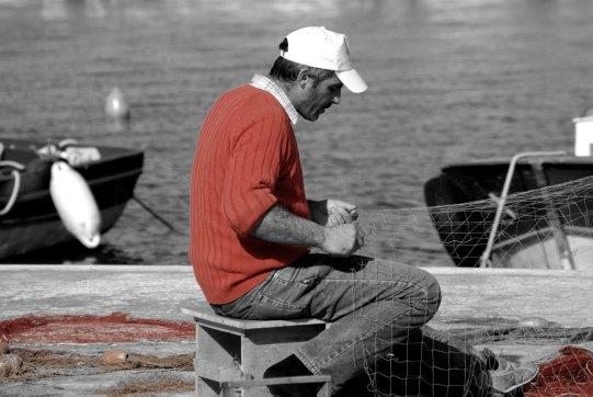 Pescatore ripara le reti