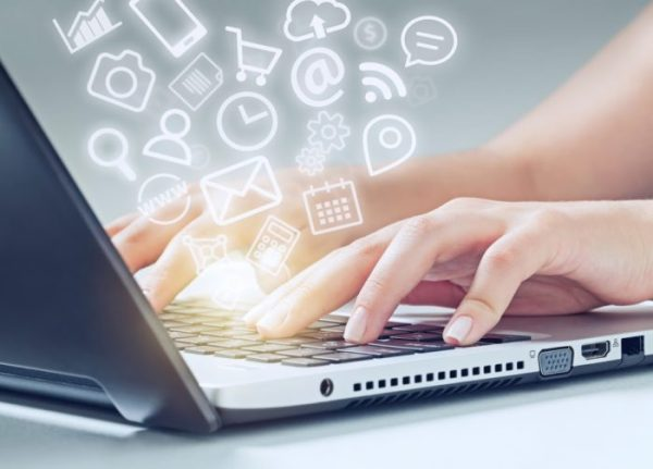 Image Of Woman Typing On A Computer With Media App Logos Flying Around - Search Influence