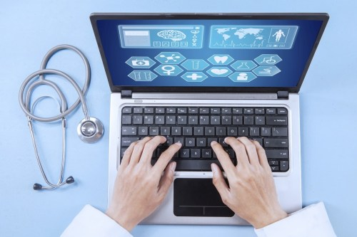 Physician typing on a laptop keyboard