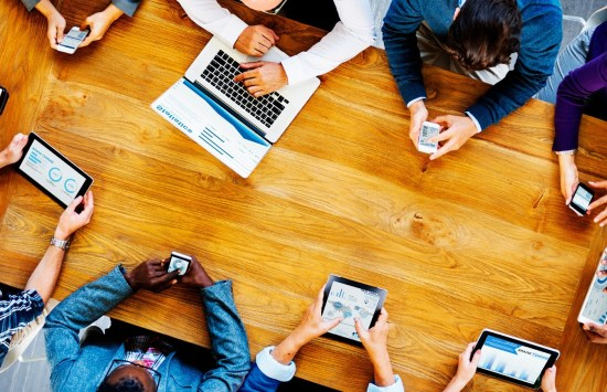 Co-workers sitting around a wooden table with electronic devices in hand - Search Influence