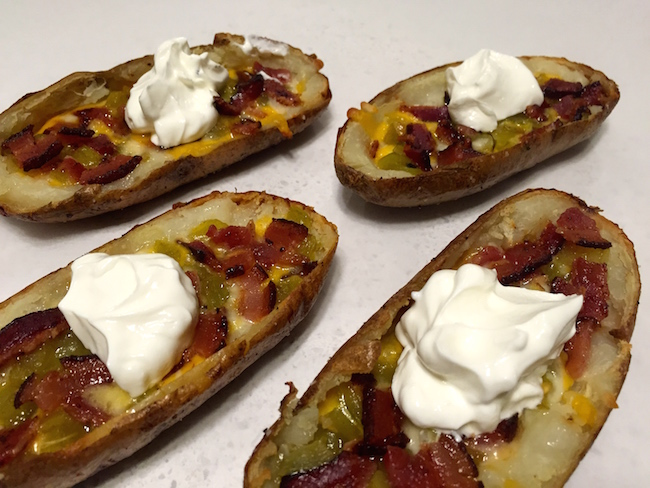 loaded baked potato skins on a weber kettle grill