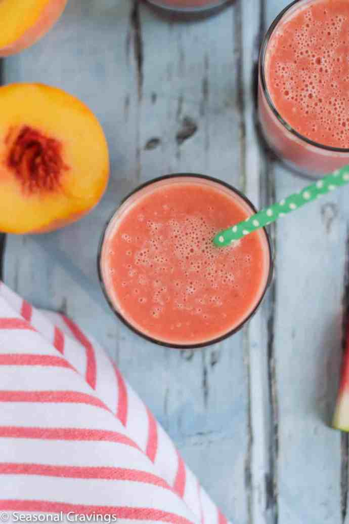 Watermelon Peach Smoothie in a glass with a green straw