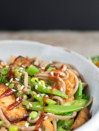 Snow pea soba noodles in a bowl on a table.