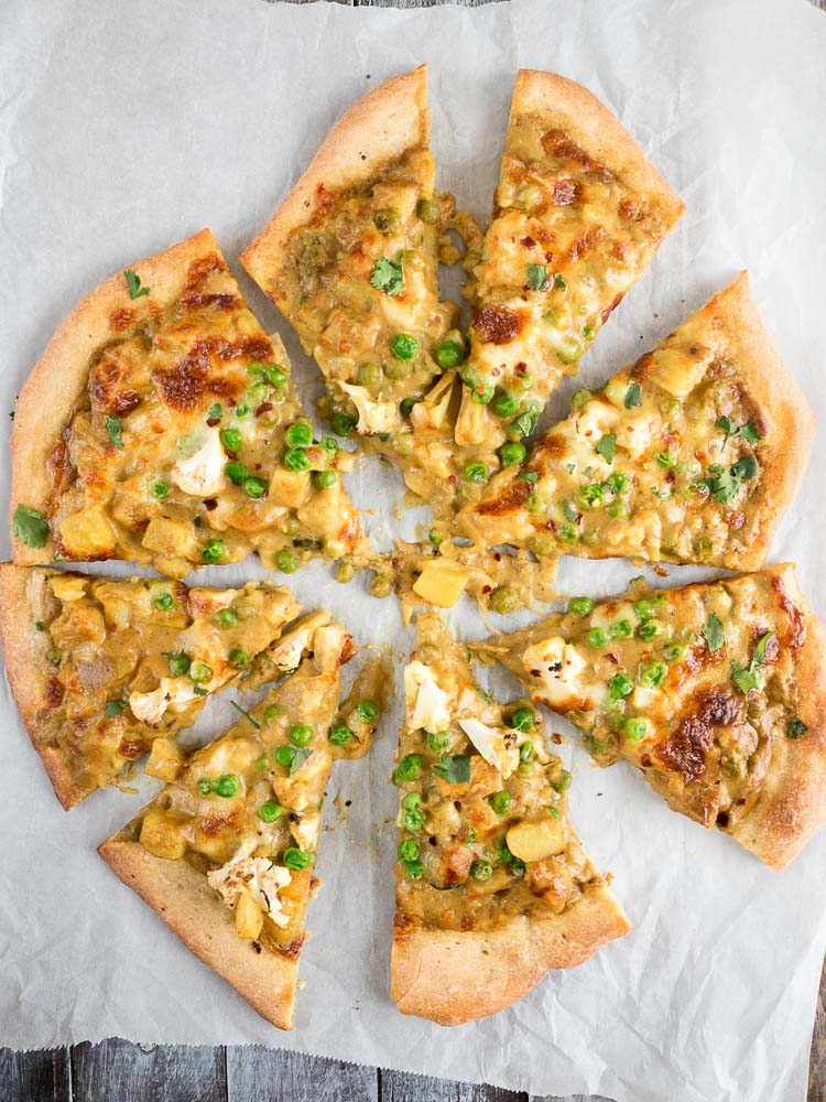Indian Pizza | A saucy Indian pizza made from leftover korma curry and topped with cheese! Rich, flavorful curry tops a crisp and doughy crust. | SeasonedVegetable.com