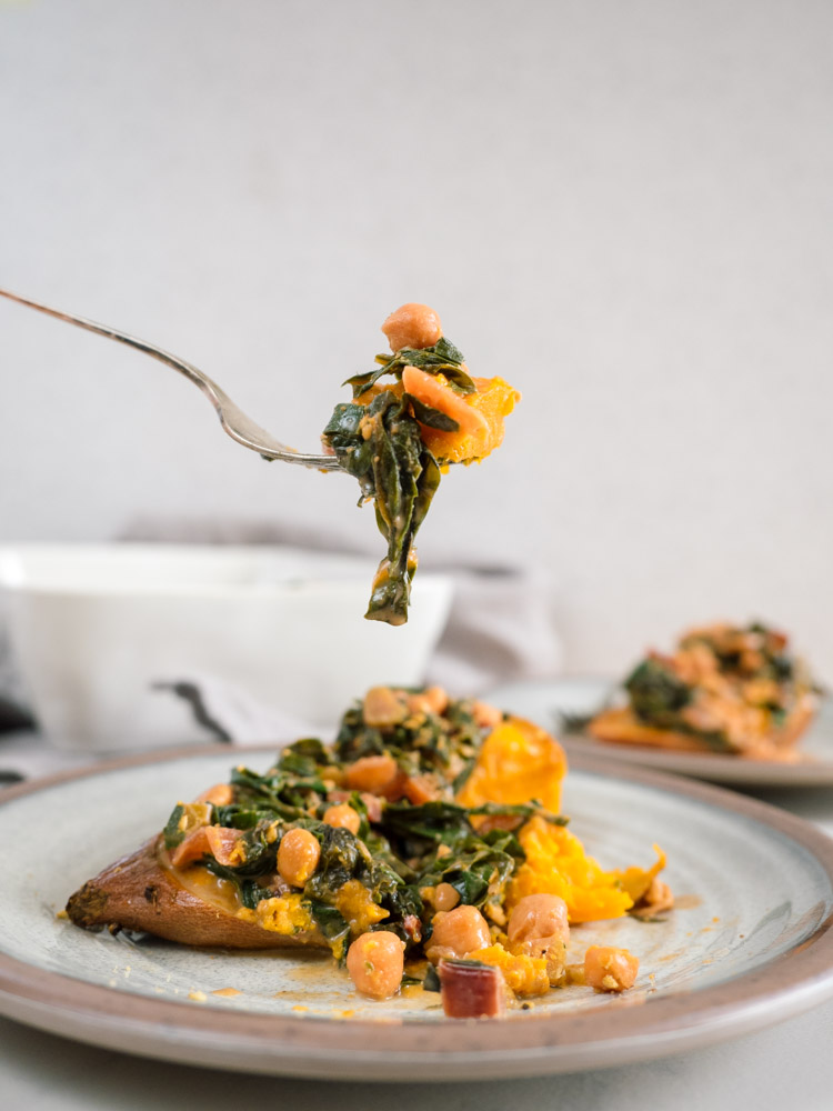 Chickpea Loaded Sweet Potato with Coconut Greens | Coconut greens and chickpea loaded sweet potatoes are the perfect winter meal. Filling, cozy, vegan and gluten free, they're packed with flavor and ready in less than an hour. | SeasonedVegetable.com #veganrecipe #savorysweetpotato #coconutmilk #glutenfreedinner #winterrecipe #vegetarianrecipe #weeknightvegetarian