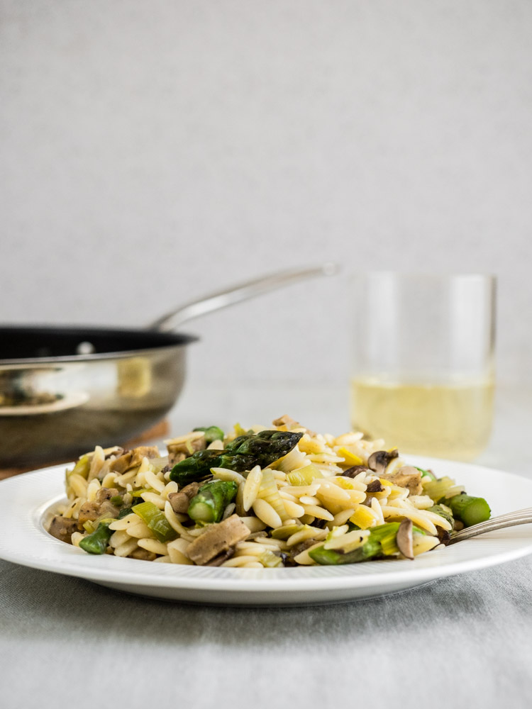 Side view of asparagus risotto with wine and cooking pan