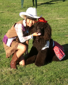 This cowgirl (Madeline) and her four-legged friend (Riley) ham it up for the photographer at an outdoor show.