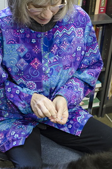 Schaefer collects some needles in her hand prior to beginning acupuncture treatment on a patient.