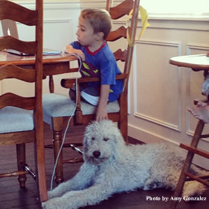 At home, Luke focuses on a math assignment while Snoopy rests patiently alongside.