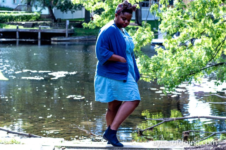 a black woman in a light blue denim dress with dark blue denim jacket in front of the mystic river